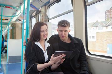 Businesswoman and businessman using digital tablet in Docklands Light Railway train, London