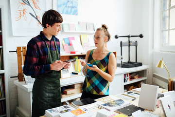 Young woman chatting to young male craftsman and using tablet technology to make purchase in art bookshop