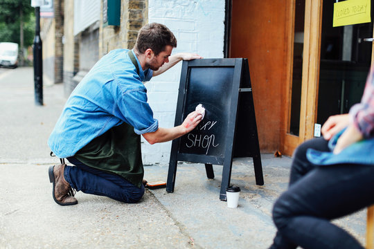 Young man kneeling on pavement and wiping blackboard outside workshop
