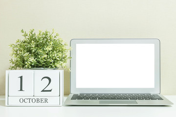 White wooden calendar with black 12 october word with white blank space at center of computer notebook on white wood desk and cream wallpaper textured background , view more date in my portfolio