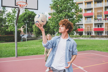 Man balancing basketball, girlfriend in background