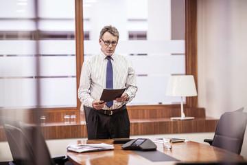 Senior businessman reading paperwork at boardroom table