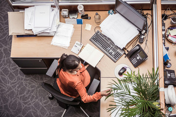 Overhead view of businesswoman busy at office desk