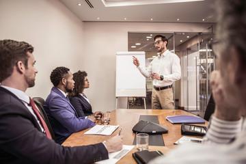 Business team listening to  flipchart presentation at boardroom table