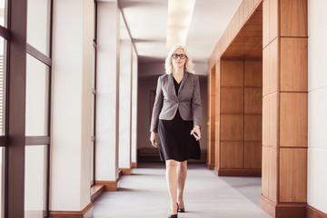 Businesswoman walking along office corridor