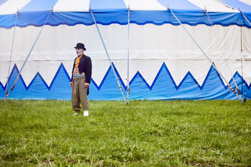 Clown standing in front of circus tent