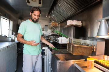 Man cooking and using smartphone in food truck