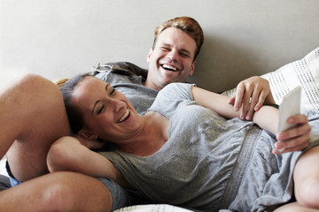 Couple reclining on bed laughing whilst reading smartphone messages