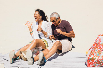 Senior couple sitting on picnic blanket on beach, laughing, Long Beach, California, USA