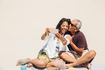 Senior couple sitting on beach, taking selfie with smartphone, Long Beach, California, USA