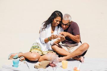 Senior couple sitting having picnic on beach, looking at smartphone, Long Beach, California, USA