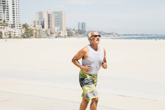 Senior man, running on beach, Long Beach, California, USA