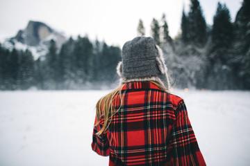 Woman wearing ushanka hat on snow-covered landscape