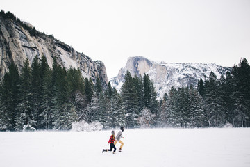 Side view of couple running on snow-covered landscape