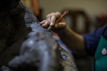 Cropped view of sculptor in artists' studio creating sculpture with hand tool