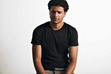 Ironic thoughtful handsome young man with an afro wearing a black sleeveless cotton t-shirt against white wall background