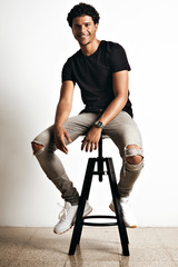 Relaxed smiling athletic young model in torn jeans, white sneakers and plain black t-shirt on a bar stool in a studio with white walls