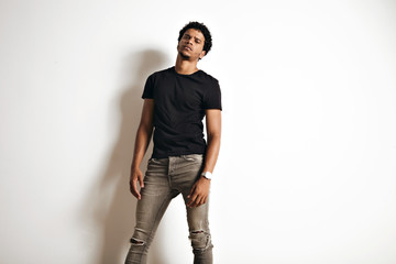 Sexy sensual gloomy looking African American model in a blank black t-shirt and skinny jeans against a white wall background