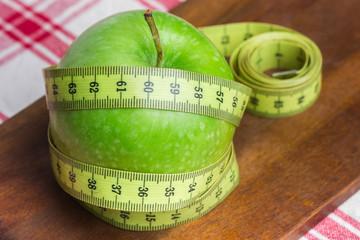 Manzana verde con cinta sobre fondo blanco (salud y concepto de dieta)