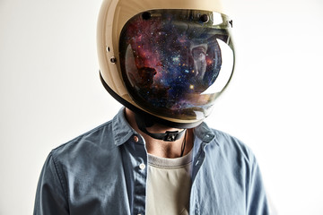 Portrait of a man in a white t-shirt and light blue denim shirt wearing a white motorcycle or space helmet with stars and galaxies reflected in the shield isolated on white. Double exposure