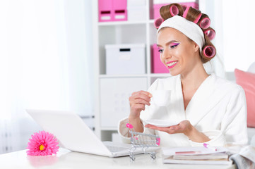 woman in hair curlers with laptop