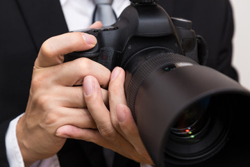 Business man with dslr camera in black suit close up