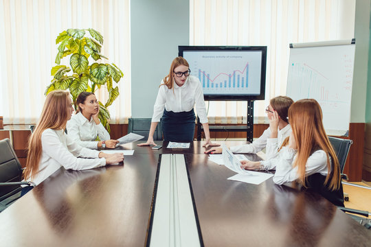 Female boss appeals to workers sitting at the table