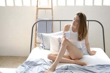 woman in bed sitd with cup of tee or coffe.