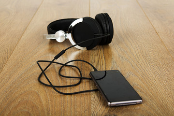 Headphones and phone on a wooden surface