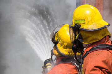 two firefighter in helmet and oxygen mask spraying water to fire