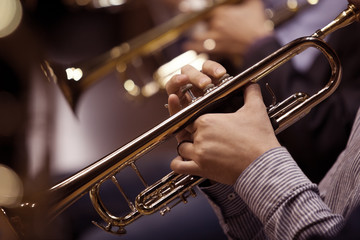 Hands of man playing the trumpet in the orchestra in dark colors