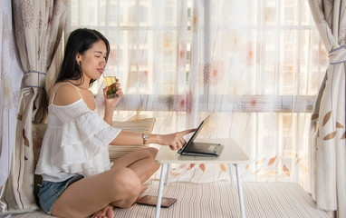 Young woman using lap top by the window