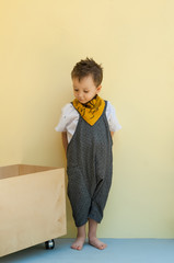 little boy in a jumpsuit with a wooden box on a yellow background