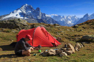 Fotomurales - Hiker cooking at his red tent in the mountains near Chamonix, France.