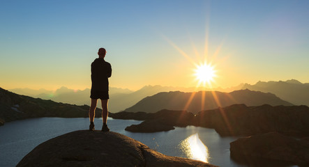 Fotomurales - Man looking over a lake, Lac Cornu, during sunset.