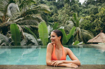 Happy young woman relaxing in swimming pool