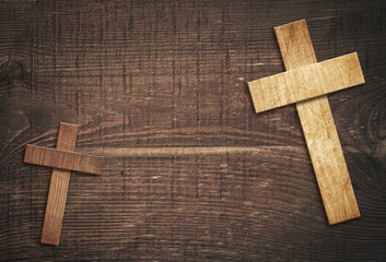 Wooden cross on brown old tabletop or wall surface