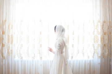 muslim woman in a white headscarf standing at the window