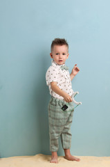 little boy in fashionable clothing and a slingshot in his hands stands on the sand on a light blue background