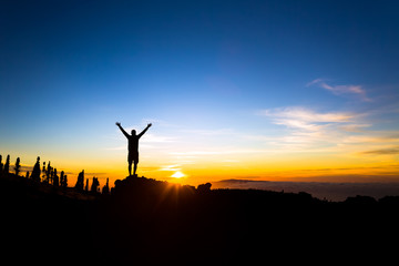 Man with arms outstretched celebrate mountains sunset