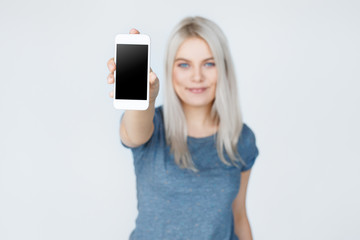Woman showing smartphone screen to the camera