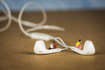 Miniature Figures Sitting on Earbuds listening to Music