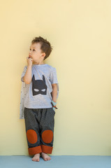 little boy in a suit with the image of Batman on a light yellow background