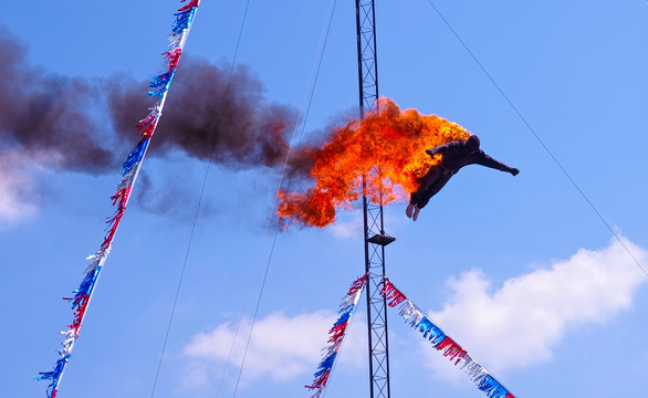 High diver daredevil performing a fire dive off a platform above a pool at a circus fair show. Stuntman in black fire protective suite. A dangerous, exciting and extreme athletic sport stunt.