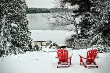 Pair of wooden adirondack chairs in the snow in front of the fro