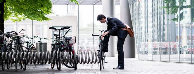 Fototapeta Businessman parking his bicycle in town obraz