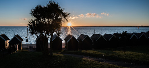 Beach Huts and Palm trees at Sunset at Gurnard, Cowes, Isle of Wight