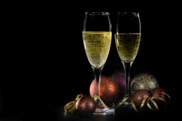 Two champagne glasses with Christmas decorations on black background. Shallow depth of field and copy space in low key still life including sparkling Christmas balls in jewel tones