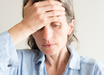 Close up of middle aged woman iwith hand on forehead covering one eye