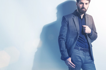Bearded businessman, suit, white wall